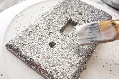 Give a plain light switch cover a glittery makeover for a splash of glitzy sparkle for a teen or tween's room. Fine glitter from a craft store, rather than chunky, old-fashioned glitter, adds sparkle with a more refined finish. Create designs with several different colors of glitter, using painter's tape or stencils to separate one section from...