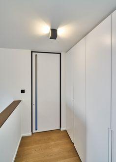 Moderne binnendeur van vloer tot plafond met een zwarte omlijsting en een ingebouwde handgreep met plexi