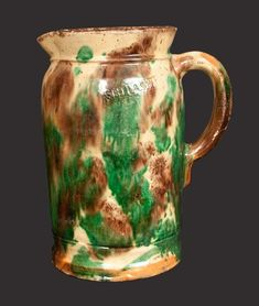 """Sold $ 1,700 Rare Multi-Glazed Redware Tankard Pitcher, Stamped """"S. BELL & SON. / STRASBURG,"""" Virginia origin, late 19th century, cylindrical pitcher with footed base, short flaring rim, and applied ribbed handle, the surface decorated with heavily-splashed green and brown glazes over a cream-colored ground. Interior covered in a reddish-brown manganese glaze. Impressed on shoulder """"S. BELL & SON. / STRASBURG"""". Exceptionally strong glaze with vivid color."""