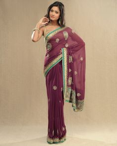 Burgundy sari with blue and gold border, embellished motifs, thin strapped gold blouse