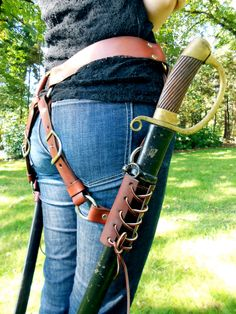 Two swords, one belt. Carry both your blades with comfort and style with this genuine leather sword belt. Symmetrical holster riggings hold one blade at each side, allowing for individual adjustment of blade height and angle. Great for men or women. Belt fits 30-36 inch waists. Holster sleeves can accommodate 1.5-2.25 inch wide scabbards.
