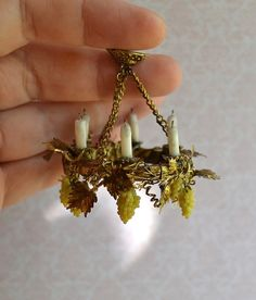 Dollhouse Miniature chandelier with candles and grapes. scale one inch, scale 1:12, miniature, chandelier, grapes. It does not shine. Imitation! Made with love! Attention! Small details, inedible, some things wires! Do not give children to play, to avoid choking and swallowing ! Not a toy, only for adult collectors! If you are looking for a unique element to add to your miniatures, this is it! The brightness and shade of the colors may be slightly different from what you see on the screen...