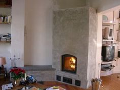 DIY Masonry Heater.  I like that it isn't squared in the room like most fireplaces.  It opens the room up more than if it were built straight like on a Lego grid.  The angle on edge at the doorway also seems to act like a funnel closing in the room for comfort, but also welcoming and drawing one in from the other room.