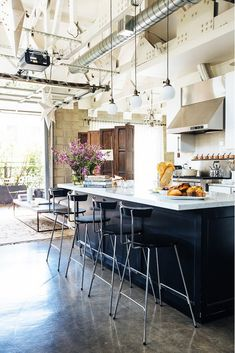 Open loft kitchen with dark island and light counters