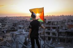 Palestinian child raises the flag of Palestine over the rubble of his ruined home because of the Israeli war on Gaza