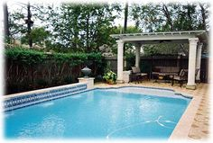 The landscaping around this in-ground pool has an elegant feel.  Classic columns support the white pergola at the shallow end - an outdoor room to relax in the shade.  Shrubs camouflage a wooden fence, and the decorative concrete pool decking has the feel of a tiled floor.  Love the mosaic wall at the left that supports a decorative urn but also houses a multi-outlet fountain that jets into the pool.  For pool installation and landscaping in Minneapolis MN, visit http://www.aldmn.com