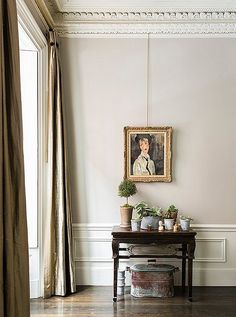 Glamorous floor-to-ceiling drapes, an antique oil paining and a vintage mahogany console table add enviable historical style to this corner vignette.