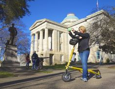 The stately North Carolina Capitol in downtown Raleigh and a Trikke rider,