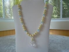 Yellow pearl beads with clear and opaque blue crystals.