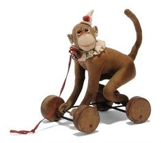 A STEIFF FELT CIRCUS MONKEY ON WHEELS, (1117ex), brown, black boot button eyes, white felt discs behind, pink felt face and ears, swivel head, wire frame with eccentric wooden wheels, white felt hat with red pom-pom, white felt ruff with bell and FF button, circa 1912 --6½in. (16.5cm.) high (some discolouration, a few moth nibbles)