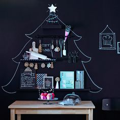 A Christmas tree has been drawn on a blackboad paint wall. Black shelves and hanging rails have been arranged across the tree and decorated with baking books, cooking utensils and cookies and muffins.