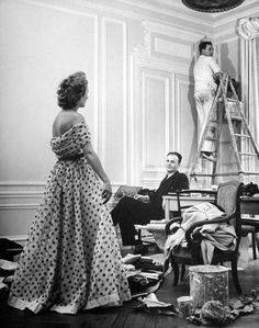 Pierre Balmain (C) observing the young lady modelling an evening dress designed by him.  Location:	Paris, France  Date taken:	February 1951  Photographer:	Nina Leen