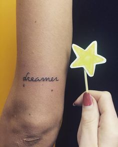 """Dreamer"" tattoo on the back of the left arm."