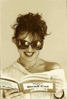"Madonna laughs while reading the snarky '80s humor classic ""101 Uses for a Dead Cat."" I hate to admit, but I read it too."