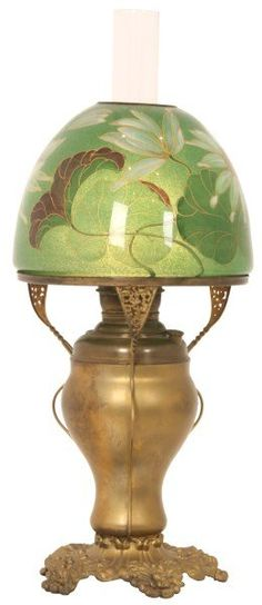 10 in. Pairpoint Water Lily Table Lamp - Portland style shade has a mushroom form, reverse decorated with a green coraline textured finish over white water lilies and dark green lily pads, has a brass aperture ring at the top. On a brass oil lamp base having a cased filigree decorated foot, 4 fancy serpentine arms reaching up along the sides, highlights at the top supporting the 10 in. brass shade ring; has an oil font which has had a single socket added in the center for electricity,