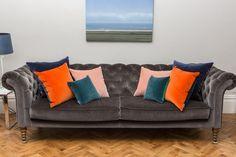 Luxe 39 Luxury Velvet Cushions in a living room. Jewel tones, Burnt orange velvet cushions, blush pink velvet cushions, teal velvet cushions and navy blue velvet cushions on a dark grey sofa. Bespoke velvet cushions UK. Small velvet cushions for colour accent in decor, large velvet cushions and velvet scatter cushions for impact. Velvet sofa cushions and velvet bolster cushions.