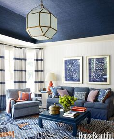 Because she needed so much curtain fabric — 80 yards — Harper used three inexpensive linens and had her workroom sew them together with bold horizontal bands of navy. Sofa in Cowtan & Tout's Crispin. Club chairs in Ferrick Mason's Lucas Check. Asilah Mosaic rug, Niba.   - HouseBeautiful.com