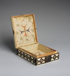 Game Box (open) ~ Italian ~ 14th century ~ Bone, wood, stain over wood core with paper and textile lining, metal mounts ~ Metropolitan Museum of Art ~ Bone and wood inlays embellish exterior of this wood box. The top is designed for backgammon or the game of tables, while the sides contain repeating lozenges with pinwheel patterns. The underside functions as a chessboard with stained bone squares, alternating green and natural bone color.
