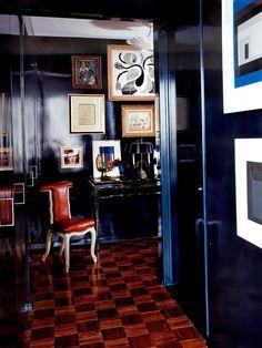 Parede azul com decoração de quadros