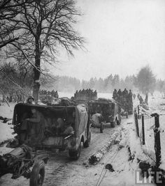Vehicles and infantry of the US 1st Army on the road during winter fighting in the Ardennes forest conflict known as the Battle of the Bulge.
