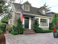 Charming Cape Cod Home Design with brick steps and bay window, two dormer windows and an American flag