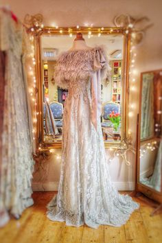 The 'Mitsou' feather and silk capelet in dove grey, shown with the 'Halcyone' embellished French lace wedding dress in French grey, both by Joanne Fleming Design