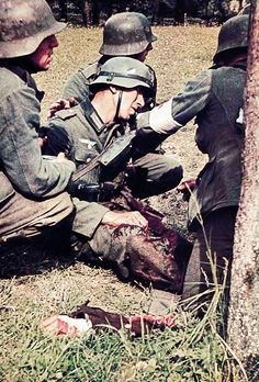A severely wounded grenadier is helped by corpsman and comrades, summer 1940, France.
