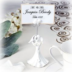 "Couple with Calla Lily Placecard Holder  Our Couple with Calla Lily Placecard Holder is made of Resin and measures 5"" H x 2"" W and holds a 2"" x 3"" placecard. #wedding #couple #favors #weddingfavors #placecard"