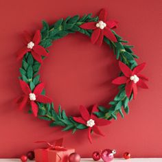 """POINSETTIA WREATH--Evergreen and ever so beautiful, our handmade felt wreath brightens your holidays with the crimson glory of the season's honorary flower, the poinsettia. Imported. 14"""" dia."""