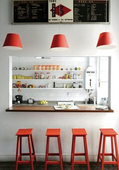 Red bar stools and lamp shades provide points of interest in the kitchen.
