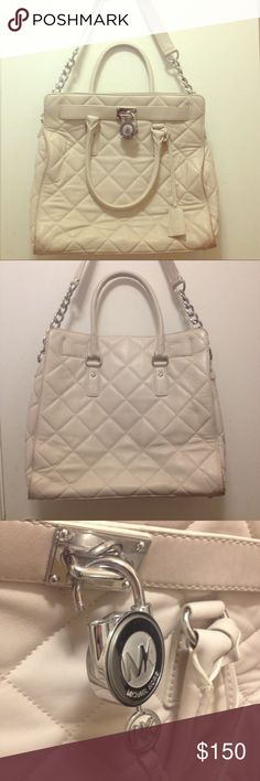 """Michael Kors handbag! This Michael Kors handbag has been loved but has plenty of life left! Bone white quilted leather bag with silver hardware, (functional) lock and key included. It has both a (non-adjustable) shoulder strap and traditional handle. Very spacious inside, too! Measurements approx: Base 14.5"""" x 4.5"""" and 13"""" tall. Main areas of wear are corners, a couple scuffs and red stain on interior zipper pocket; all pictured above. 100% authentic! NO trades! 😊👜 Michael Kors Bags"""