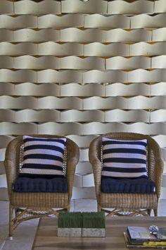Entre as linhas mais marcantes está a Trama, inspirada nas ondas do mar, a qual me atrevo a relacionar com Oscar Niemeyer, não por suas curvas, mas por ressaltar a idéia que arquiteto sempre empregava em seus projetos, onde o importante não são os elemento e sim o espaço entre eles e a forma como ocupam o espaço. Trama - Peças cimentícias de 30x70x5cm, disponível em 7 cores.