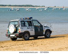 SANLUCA, SPAIN - AUGUST 18: Police car on patrol at the beach August 18, 2009 in Sanluca, Andalusia, Spain. This is to prevent drugs smuggling and illegal immigration. - stock photo