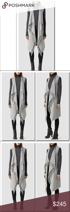 """All Saints Paxton Sleeveless Coat in Pale Gray Make the transition through the seasons a seamless one in this chic knitted coat by AllSaints. This deconstructed style is designed with a open waterfall front and detailed with a tassel hem and a waist belt to close. Crafted from a cosy wool blend, this sleeveless unlined piece is perfect for layering. Wear yours over a roll neck top and pair with dark denim for off-duty chic.  Length Back 39"""" - longest point 45"""" 60%Wool 40% Polyester Blend Dry…"""
