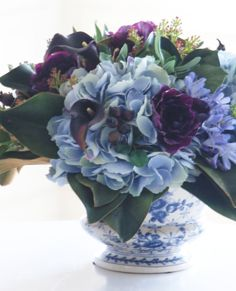 Clusters of handcrafted silk polyester hydrangeas, calla lilies, and poppies sit on a bed of magnolia leaves, complemented by sprigs of pittosporum leaves and lilacs.