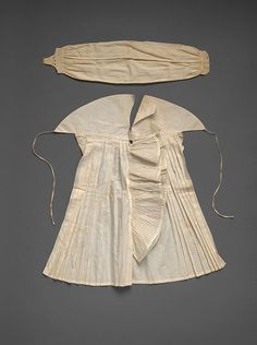 """Shirt Front"" and Stock A false shirt front, or what we would now call a ""dickey,"" was a cost-effective strategy to extend the use of a shirt. Stocks were rectangles of fine linen, arranged in small pleats and sewn into linen tabs which fastened around the neck with a metal stock buckle. In the 1800s, the stock was replaced in fashionable dress with the cravat. Some older men retained their stocks long after they went out of style."
