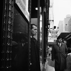 A man standing in a doorway cigarette in mouth, with another man about to pass by him on the street with a fire escape rising up vertically from a Sargent's sign. VM1966W01174-04-MC