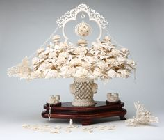 A Chinese carved ivory floral bouquet, Elaborately carved and naturalistically modeled as a pierced basket overflowing with flowers surmounted by an arched frame with puzzle-ball pendant, on a stained wood stand.