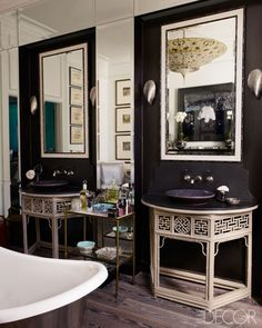 Fashion editor Kim Hersov's master bathroom. In the master bath, demilune tables are fitted with Kohler sinks and Lefroy Brooks fixtures, the sconces are by Porta Romana, and the walls are painted in Farrow & Ball's Mahogany.