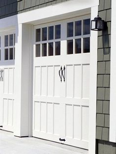 "love old carriage house style garage doors! i also like the darker gray siding with the crisp white trim. ""Sectional doors can feature windows in an upper panel, and some higher-end versions can mimic the look of traditional carriage-house doors."""