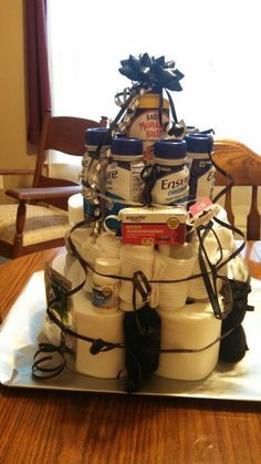 """Funny 60th Birthday Gift Idea for Dad. Collect together items that just say """"old"""" like adult diapers and stomach pills. Then make into a cake design. This will go down well when presented at a birthday party."""