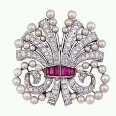 Platinum Set Diamond, Ruby & Pearl Brooch circa 1945 Brooch contains 70 round brilliant-cut diamonds (1.94 ct total wgt.), 6 rectagular step-cut rubies (approximately 0.91 ct total wgt.)  & 36 round white & off-white cultured pearls. Measures 1 5/8 in. long.