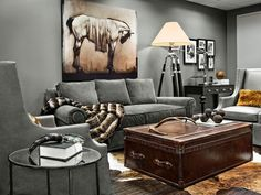 Gray walls and matching gray upholstered furniture allows the accessories to stand out in this living room. A horse painting is illuminated by a black tripod lamp with a cream lampshade. A brown leather trunk doubles as a coffee table and ottoman, contributing to the masculine design.