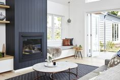Real reno: California bungalow now bathed in sunshine - The Interiors Addict. Love the striking dark fireplace with vertical shiplap Home Fireplace, Living Room With Fireplace, Fireplace Design, Living Room Decor, Shiplap Fireplace, Fireplaces, Fireplace Kitchen, Scandinavian Fireplace, Scandinavian Interior
