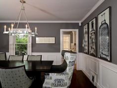 Chairs with playful, colorful patterns dress up a black dining room table. The room's gray walls are anything but boring and neutral thanks to large art prints of bottles and white wainscoting and crown molding.