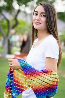 """I am in love with Knit Picks Chroma Fingering, a gorgeous, soft, self-striping yarn! I designed this Shawl with the colorway Carnival to highlight the beautiful rainbow shades with a lovely, lacy stitch pattern. It is 11"""" wide and made to be worn as an off the shoulder wrap. Adjust length as desired. You will love this yarn and pattern."""