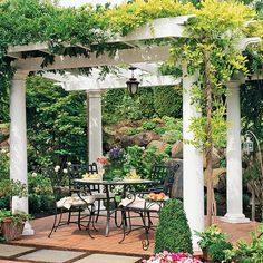 A pergola - I so want to put one of these out back by the pool!  I am particularly in love with the columns and the light fixture.  Adding the trees and shrubs creates a special defined space. Of course the pic has the wonderful rock garden behind it as well.....looks like a relaxing place to have AM coffee, or spend time with friends after dinner....ahhh!