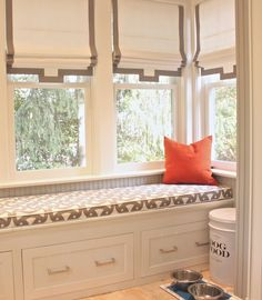 source: Laura Tutun Interiors  White and gray mudroom features built-in window seat with drawers covered in white and gray geometric cushion situated under windows dressed in white and gray roman shades.