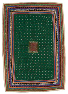 Dharki quilt, Mutwa People, made in Banni, Kutch, Gujarat, India, circa 1975-2000, 82 x 59 in.  Rabari are perhaps the best known tribe in Gujarat, but many other groups call this part of India home. One such group is the Mutwa (or Mutava), who are Muslims. This typical Mutwa quilt has a large central field with an embroidered medallion in the middle. Smaller, evenly spaced embroidered motifs, shisha work (tiny mirrors attached with embroidered stitches) and multiple multi-colored borders