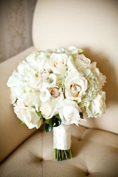 "The bridal bouquet will be a clutch of cream hydrangeas, ""Juliet"" garden roses, ""café au lait"" dahlias, and ivory spray roses wrapped in ivory ribbon with the stems showing."